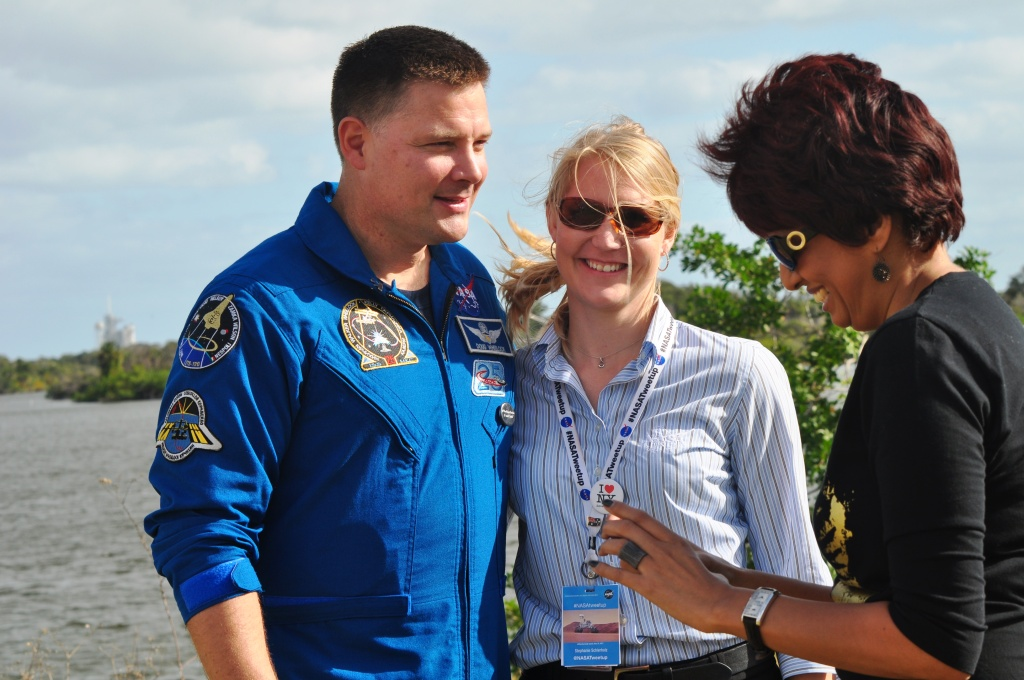 NASA Astronaut Doug Wheelock Poses with NASA's Social Media Manager Stephanie Schierholz While Gabrielle Laine-Peters Reviews Photo She Snapped Highlighting #SchierholzFanClub Button Given by Annie Wynn, Kennedy Space Center, Fla., Nov. 26, 2011