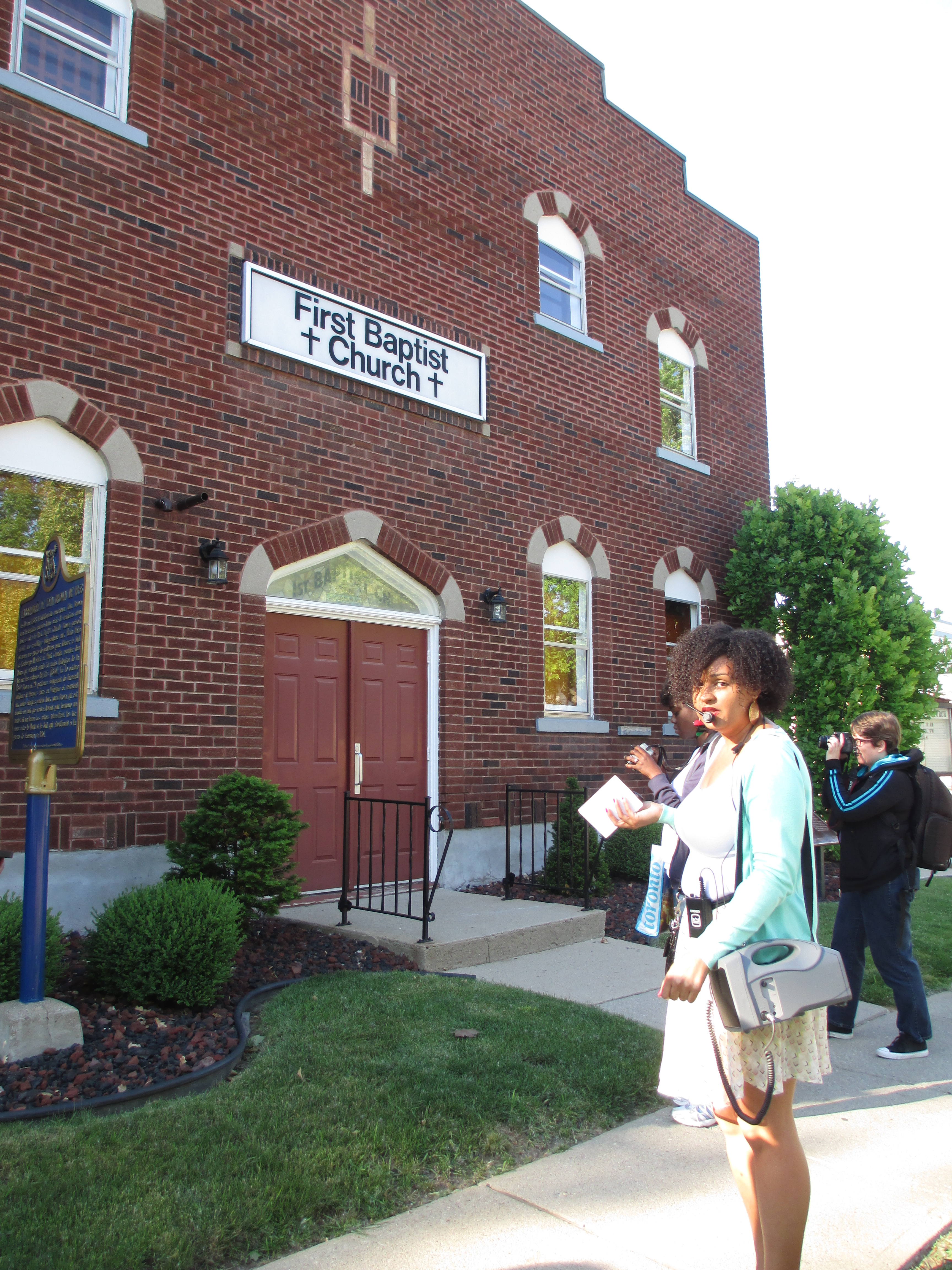 Ms. Blair Newby stops in front of the First Baptist Church in Chatham where John Brown held a convention and finalized plans to attack Harpers Ferry.